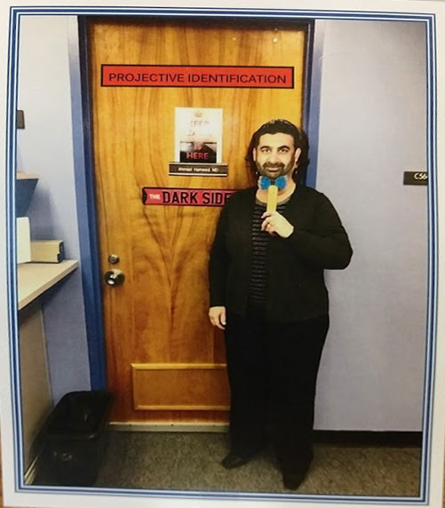 A person holding up a mask is seen standing in front of an office door labeled Projective Identification - The Dark Side.