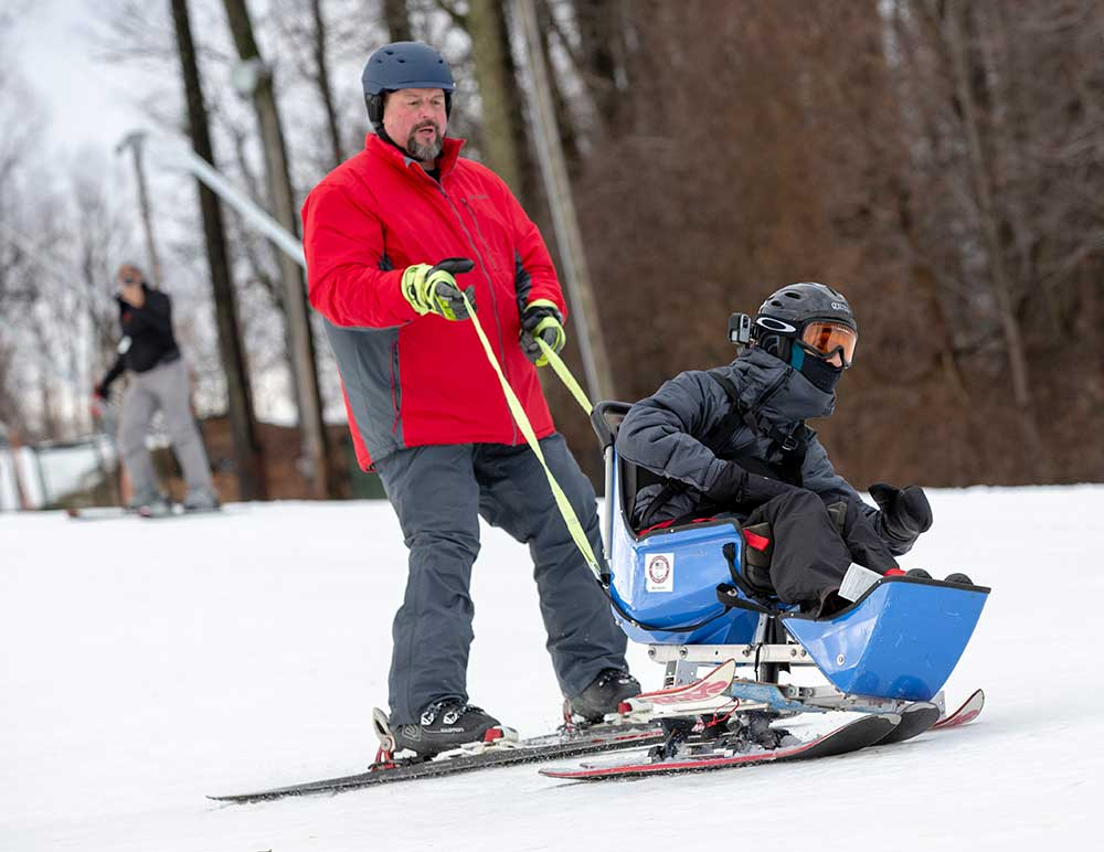 A man in a parka on a pair of skis holds onto straps behind a man in goggles and winter wear in a plastic seat outfitted with skis. Both men are sliding on snow with bare trees in the background.