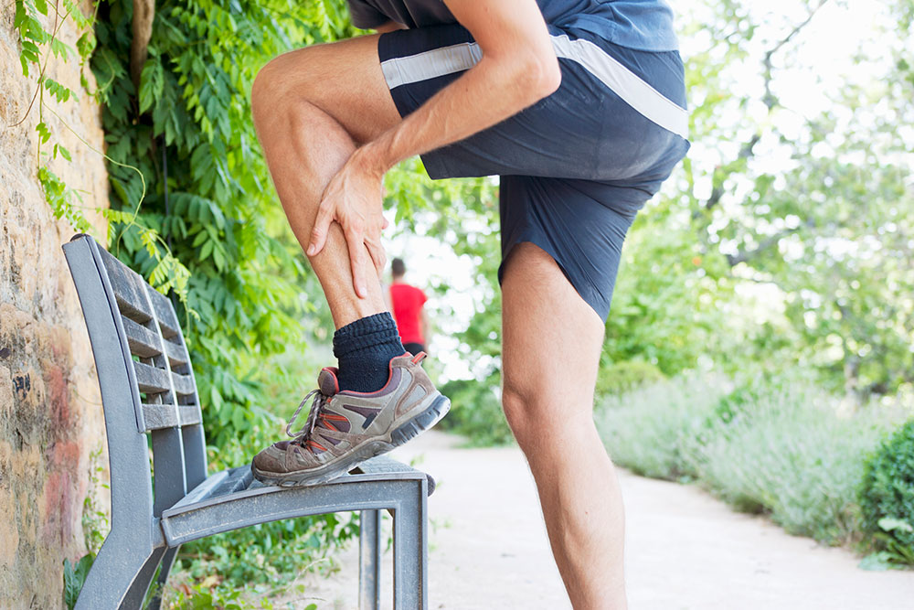 A male runner stretches left calf muscle on a bench in a stock photo.
