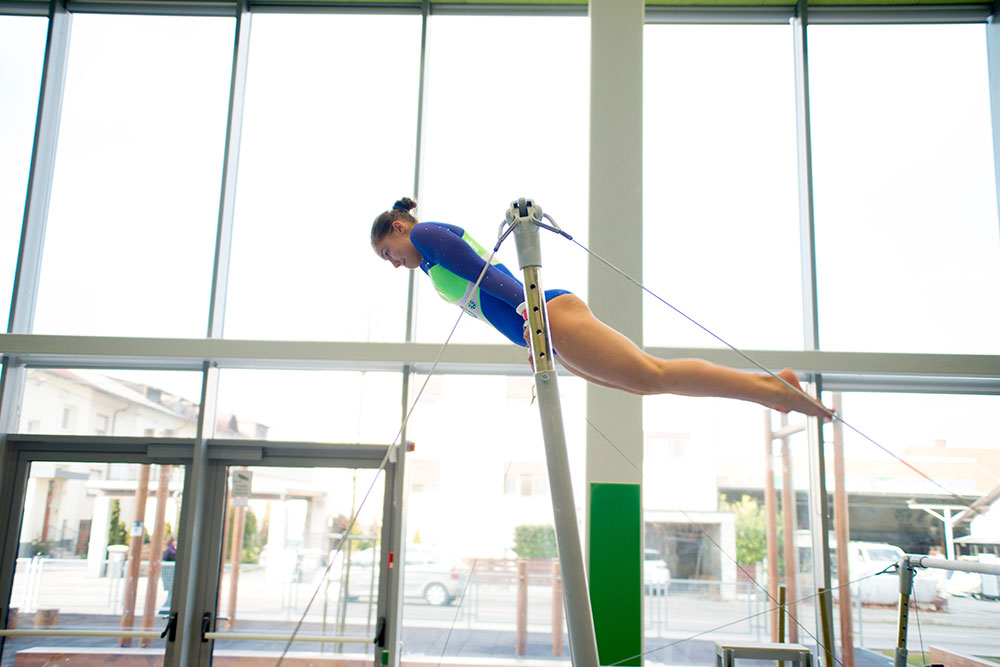 A female gymnast is seen on the uneven bars in a stock photo.