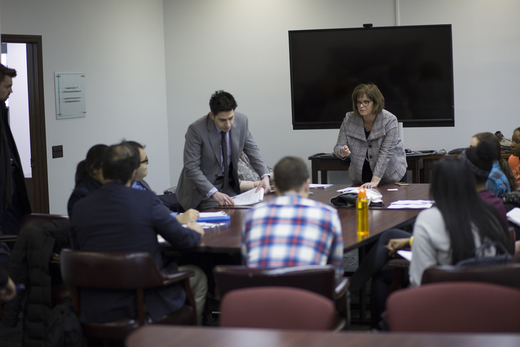 A woman in business attire is seen standing in front of a room, leaning on a table and gesturing. Students are seen sitting facing the woman.
