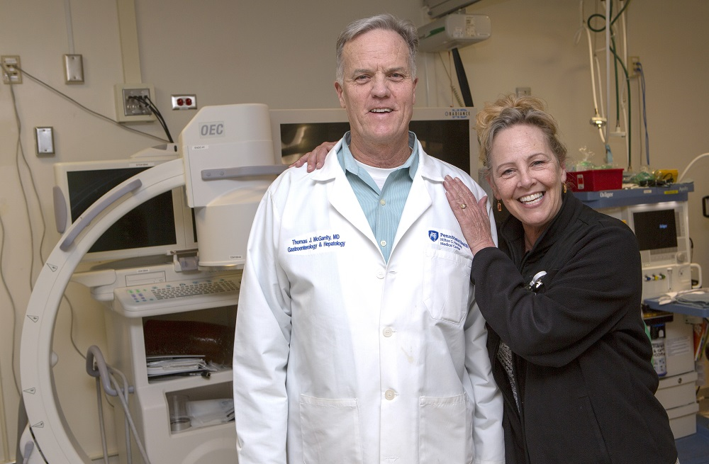 "Bobbie Mann of Lebanon, Pa., smiles with her arm around Dr. Thomas McGarrity, a gastroenterologist at Penn State Health Milton S. Hershey Medical Center. She has blonde hair and is wearing a sweatshirt. Dr. McGarrity is wearing a white lab coat with the Medical Center logo on the right and his name and ""Gastroenterology & Hepatology"" on the left. They are standing in front of a colonoscope and three monitors."