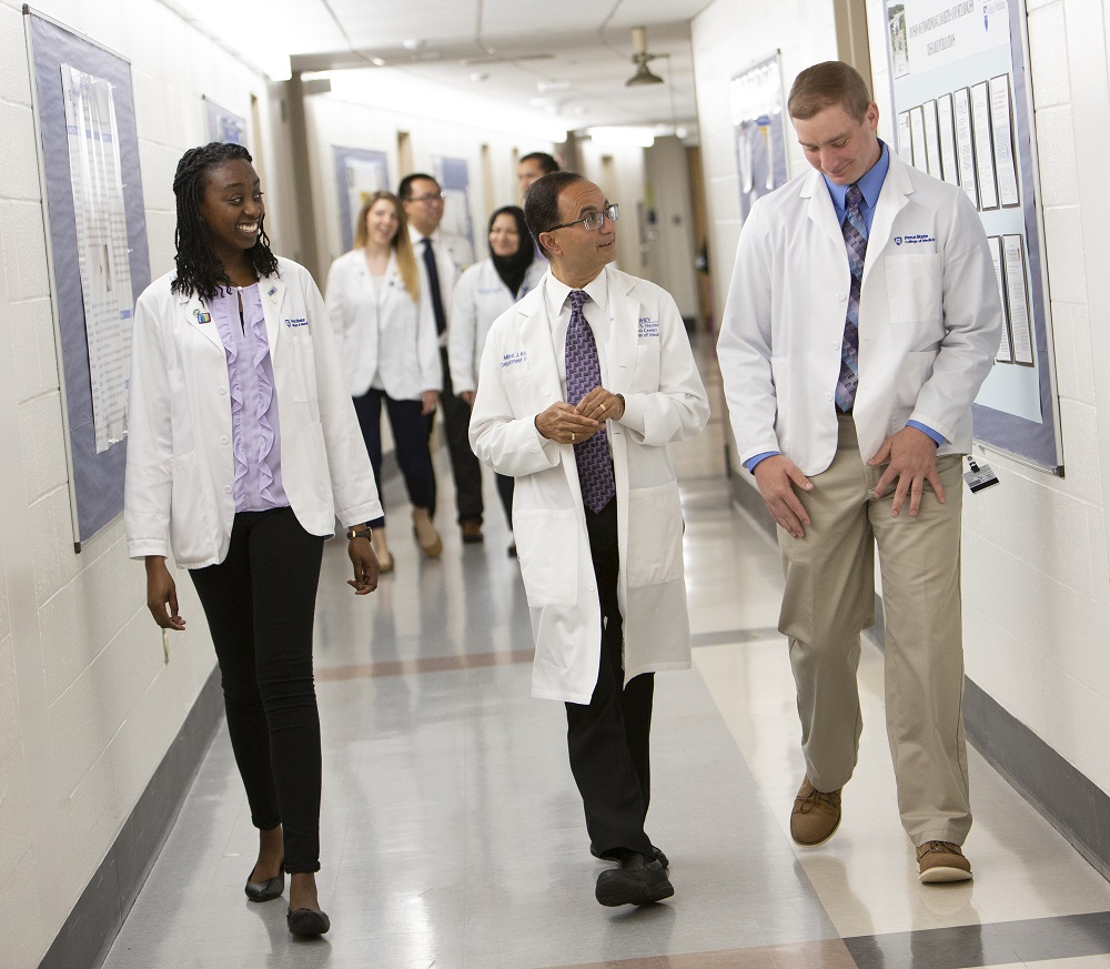 Two men and a woman in white lab coats walk through a tile-floored hallway. Another group of four people are in the background behind them.