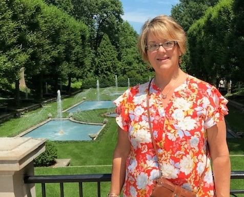 A woman wearing an orange blouse with white flower pattern stands in front of a railing with a green lawn and fountains in the background.