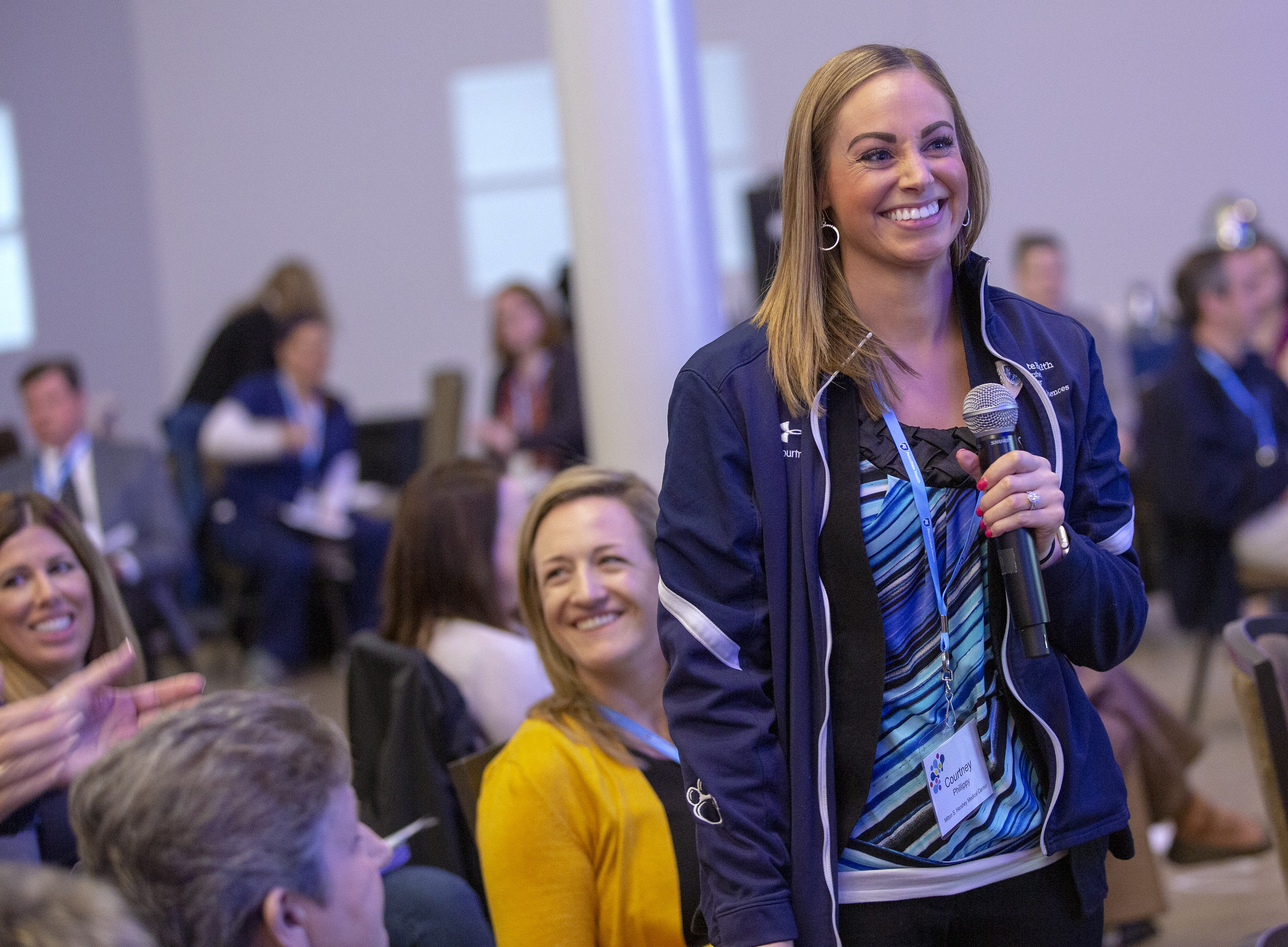 Courtney Phillippy, a woman with long, blonde hair, stands with a microphone in her hand and smiles during a small group session at the 2019 Leadership Conference: This is Penn State Health. She is wearing a Penn State jacket and a striped top. Behind her other employees smile or look to the side. A large steel column is behind her.