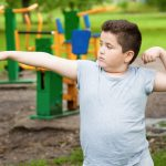 A young boy stands with his right arm extended outward and his left arm curled upward. Playground equipment is in the background.