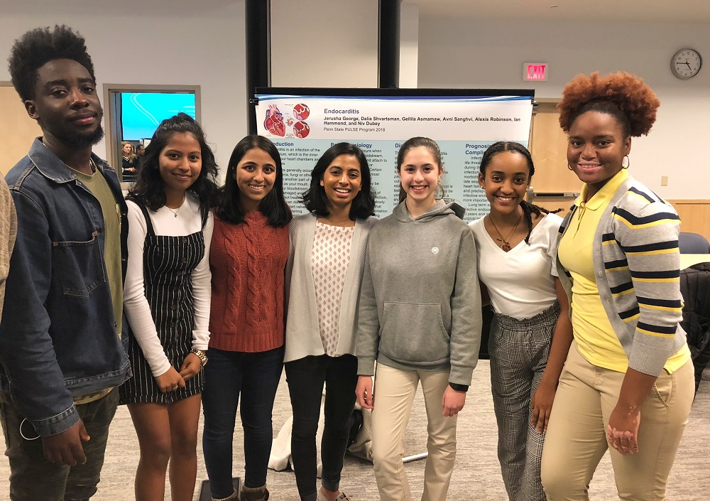 Seven high school students who won the 2018 poster session at Penn State College of Medicine's PULSE program smile in front of a poster presentation on endocarditis. One young man and six young women stand in a row and smile. They are dressed in casual clothes. Behind them on the left several people are visible through a doorway.