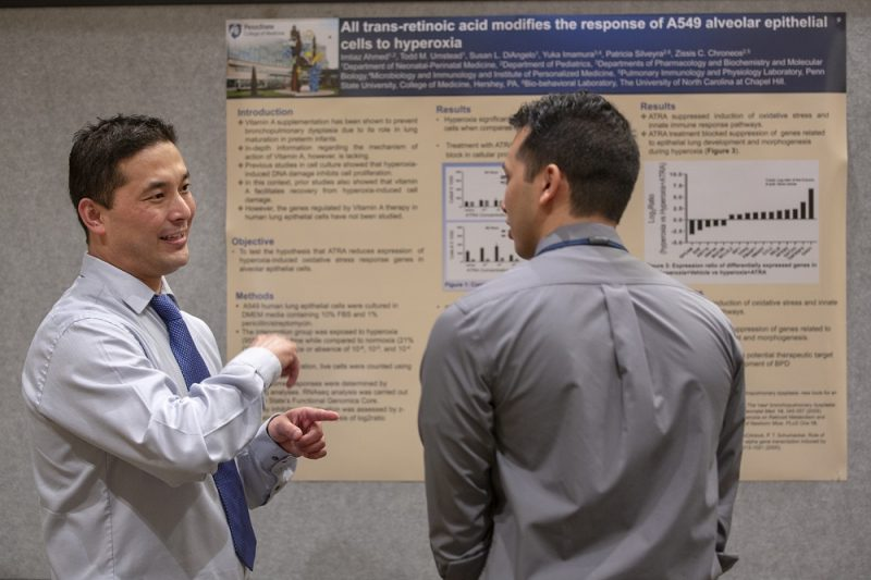 "Two men speak to one another in front of a poster with the words ""All trans-retinoic acid modifies the response of A549 alveolar epithelial cells to hyperoxia. The man wears a tie and gestures. The man on the right is facing the poster with his head turned toward the gesturing man."