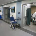 A physician and two other care providers treat a patient who is lying in a bed in Hershey Medical Center's new Radiology Outpatient Care Unit. A long hallway with a tiled floor shows five rooms. The care providers and patient are in the room on the right, which has a curtain and a door. A wheelchair is outside the door. Paintings are on the walls between each room. Medical waste containers are outside each room.