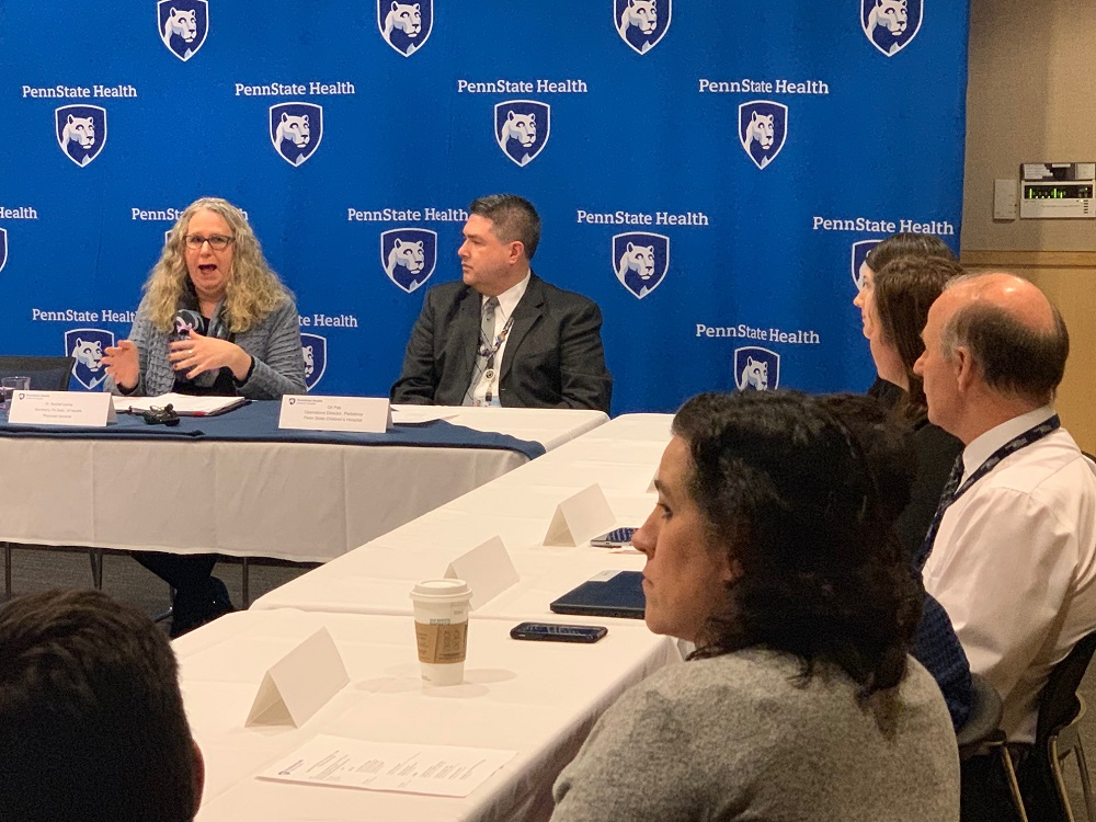 Pennsylvania Health Secretary Dr. Rachel Levine speaks in front of a screen featuring the Penn State Health logo, while seated at a conference table. Other men and women seated at the table watch her.