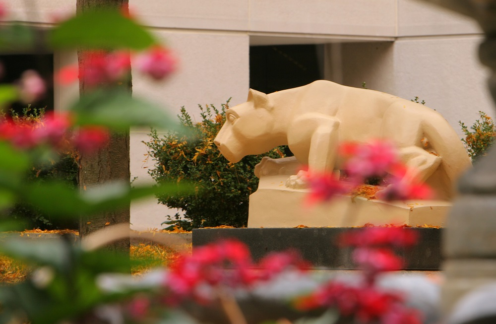 A statue of the Nittany Lion looks toward some flowering bushes. In the foreground, flowers are blooming.