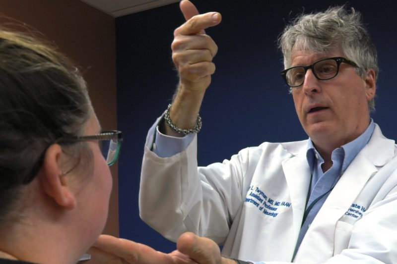 Dr. Cary Twyman, a neurologist at Penn State Health, examines a patient. He stands in front of her, his left hand on her chin, his right hand extended slightly into the air.