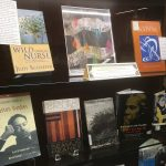 Display case with books. Includes Wild Onion Nurse by Judy Schaefer and Sharing the Solitude by Patrick Quinn.