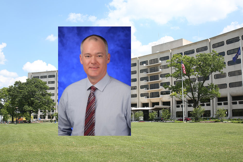 A head-and-shoulders professional photo of Dr. Douglas Leslie is superimposed on an image of Penn State College of Medicine's Crescent building in Hershey, PA.