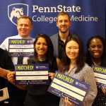 "A group of seven people is seen standing in front of a Penn State College of Medicine banner. The students in the middle are holding signs that say ""I Matched!"" and that list residency location and specialty."