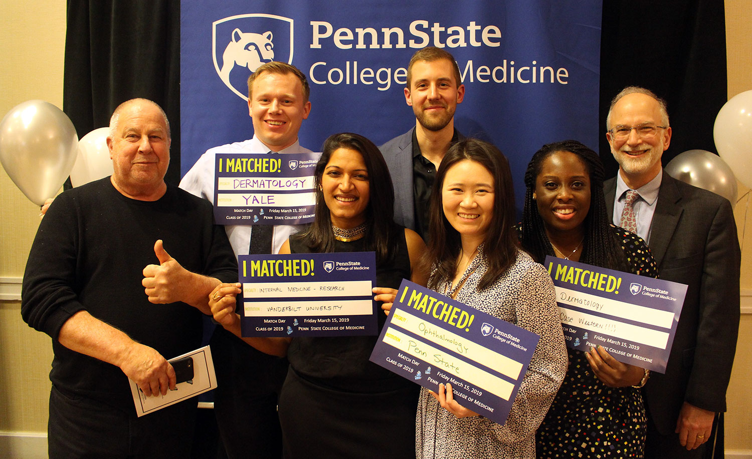 A group of seven people is seen standing in front of a Penn State College of Medicine banner. The students in the middle are holding signs that say
