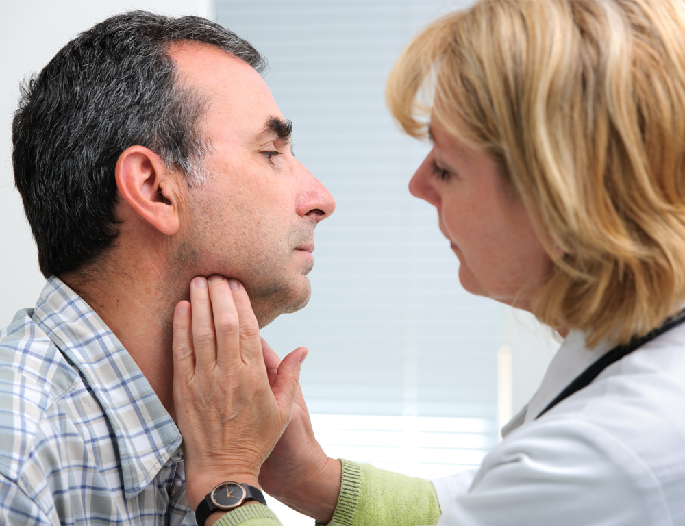 A female physician wearing a white coat and stethoscope places both hands on the throat region of a male patient.