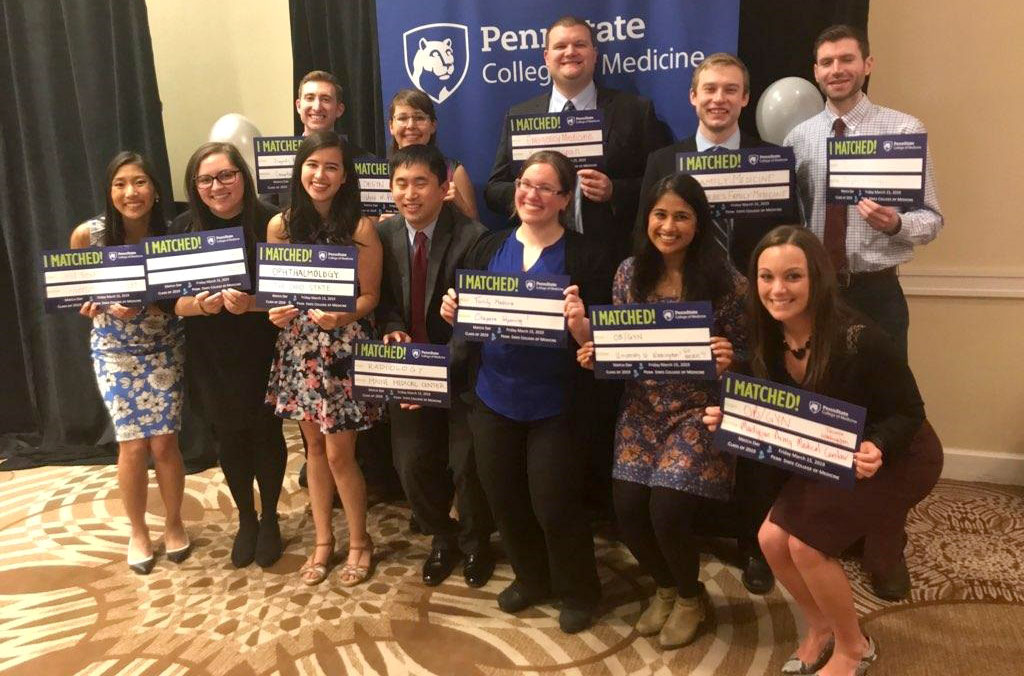 A group of Penn State College of Medicine students is pictured in front of a banner with the College logo on it. The students are each holding a sign showing the institution and speciality in which they will be completing residency.
