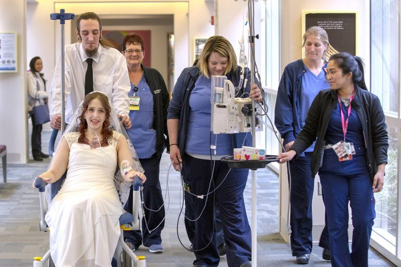 A man in a white shirt and black tie pushes a woman in a wedding gown in a wheelchair down a hospital corridor. With him are several members of the hospital staff in blue nurse's uniforms. The nurse in the center wheels a tall stand from which dangle wires which are attached to the woman in the gown.