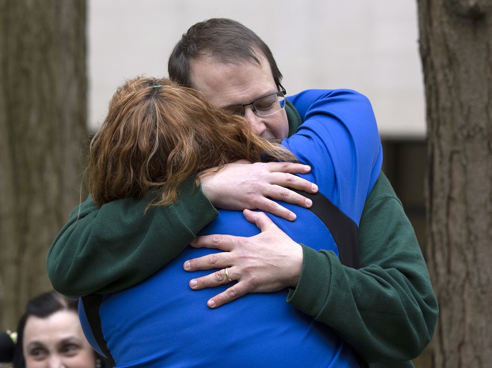 Bill Griffis' eyes are closed behind his glasses as he embraces Brooke Olenowski, whose back is facing the camera. They are bracketed by two trees in the background, where another woman looks on.