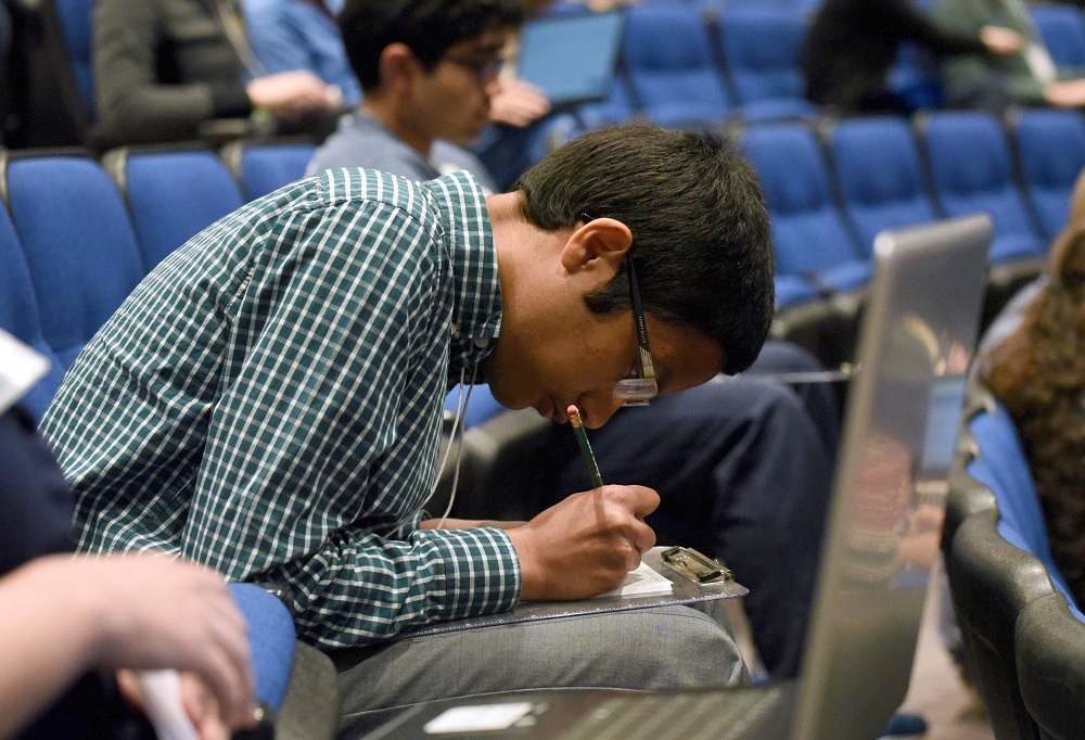 Cedar Cliff High School junior Thussentham Walter-Angelo, winner of the 2019 Central PA Regional Brain Bee, bends over a clipboard on his lap and writes answers during the 2019 USA National Brain Bee, held April 12-14 at Penn State College of Medicine. He is seated in an auditorium, surrounded by other students. He wears a plaid shirt, gray pants and glasses.