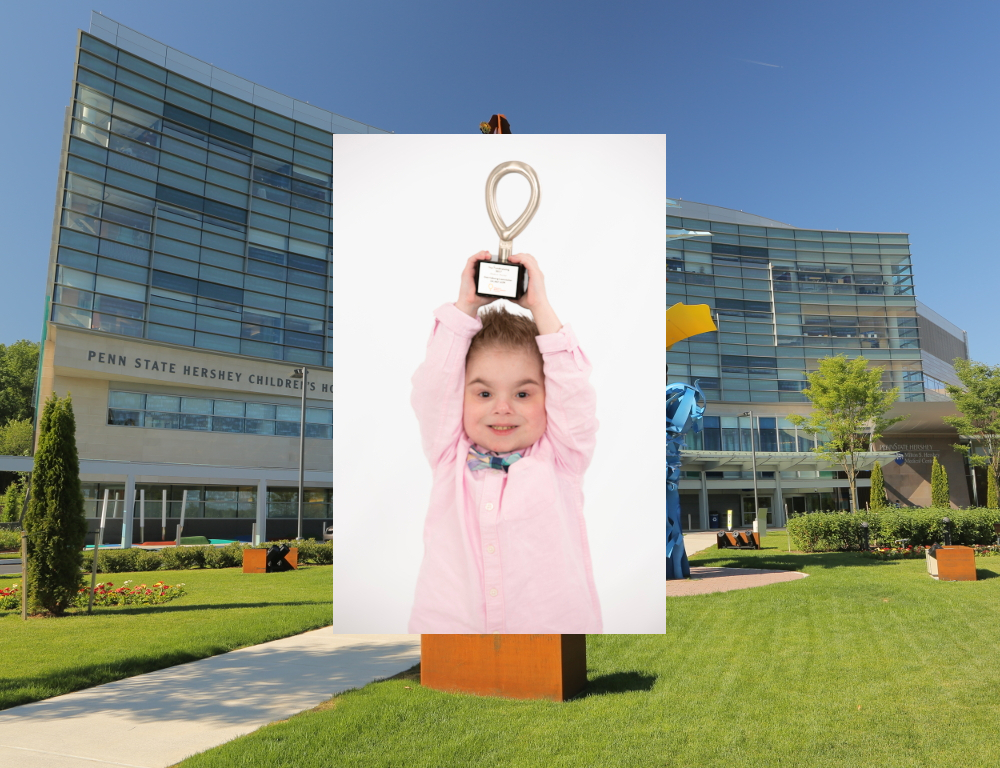 A portrait of a young boy holding a CMN trophy above his head, superimposed over an image of Penn State Children's Hospital.