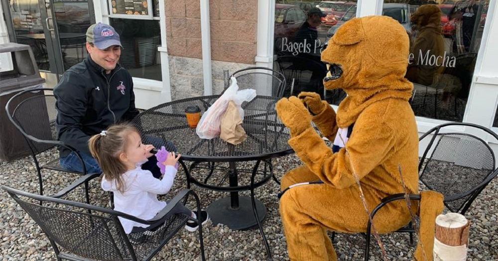 A person dressed as the Penn State Nittany Lion sits at an outdoor table with a little girl and a man in a jacket and a ball cap. They are reflected in the window of a shop advertising bagels.