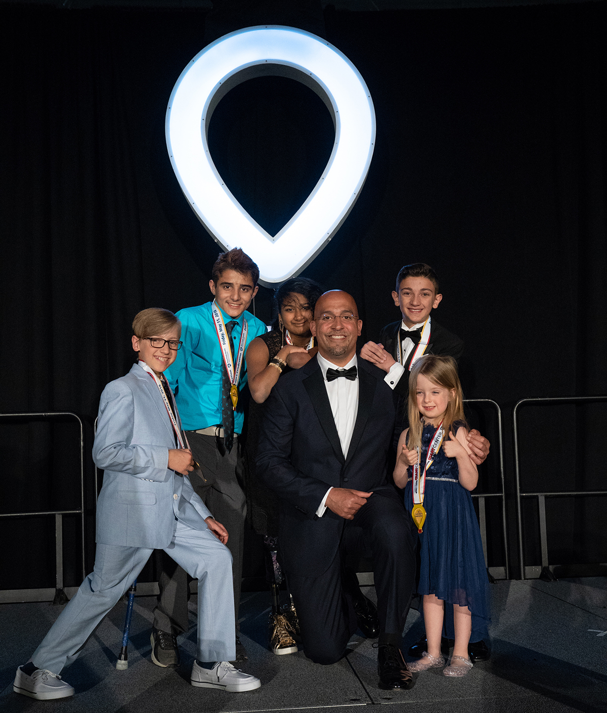 Penn State Football Coach James Franklin, wearing a tuxedo, kneels on one knee. Around him are five young children. An illuminated CMN logo is in the background.