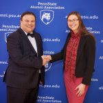 A woman in a dress and blazer shakes hands with a man in a suit with a bow tie. Behind them is a surface covered in the logo and web address for the Penn State Alumni Association.