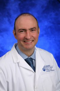 Dr. Sinisa Dovat smiles. He wears a white jacket with the Penn State Health Milton S. Hershey Medical Center and Penn State College of Medicine logo on the breast, a sport shirt and tie.