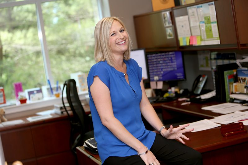 Adrienne Bruner of Penn State Health Human Resources sits on the edge of a wooden desk and smiles at the camera. She has blonde hair and is wearing a short-sleeved top and pants. Behind her is a chair, a computer and a window with trees visible outdoors. Papers are on the desk and credenza.