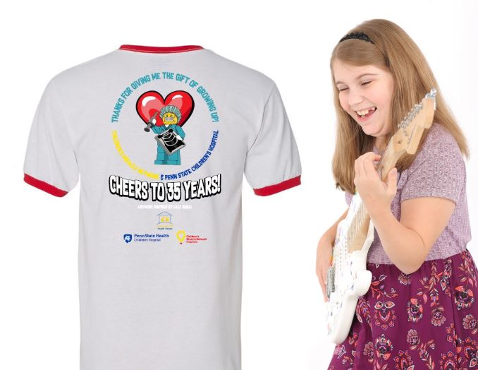 """Children's Miracle Network mriacle child Lilly playing the guitar and smiling. A t-shirt is displaying text """"thanks for giving me the gift of growing up, cheers to 35 years"""" which is the 35th anniversary of CMN."""