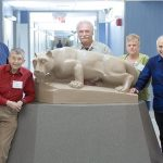 "Penn State College of Medicine's Mini Medical School participants, from left, ""Sir"" Robert Griscavage, Bonifacio Dewasse, Robert Hairston, Ruth Miller, William Miller, Rebekah Miller, Perry Emes, Marylou Martz and Joan Decker pose in front of a Nittany Lion statue in the rotunda of Hershey Medical Center. Behind them a hallway is visible."