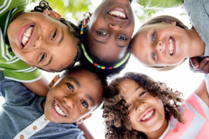 Five young children put their heads together, standing in a circle and looking downward at the camera. They are all smiling.