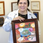 Dr. Zakiyah Kadry of Hershey Medical Center holds an oil painting created for her by a patient. She is wearing a white lab coat, top and gold necklace. The painting is in a wooden frame and shows flowers, Don Quixote, a coffee cup and a thank you note. Behind her are diplomas and plaques.