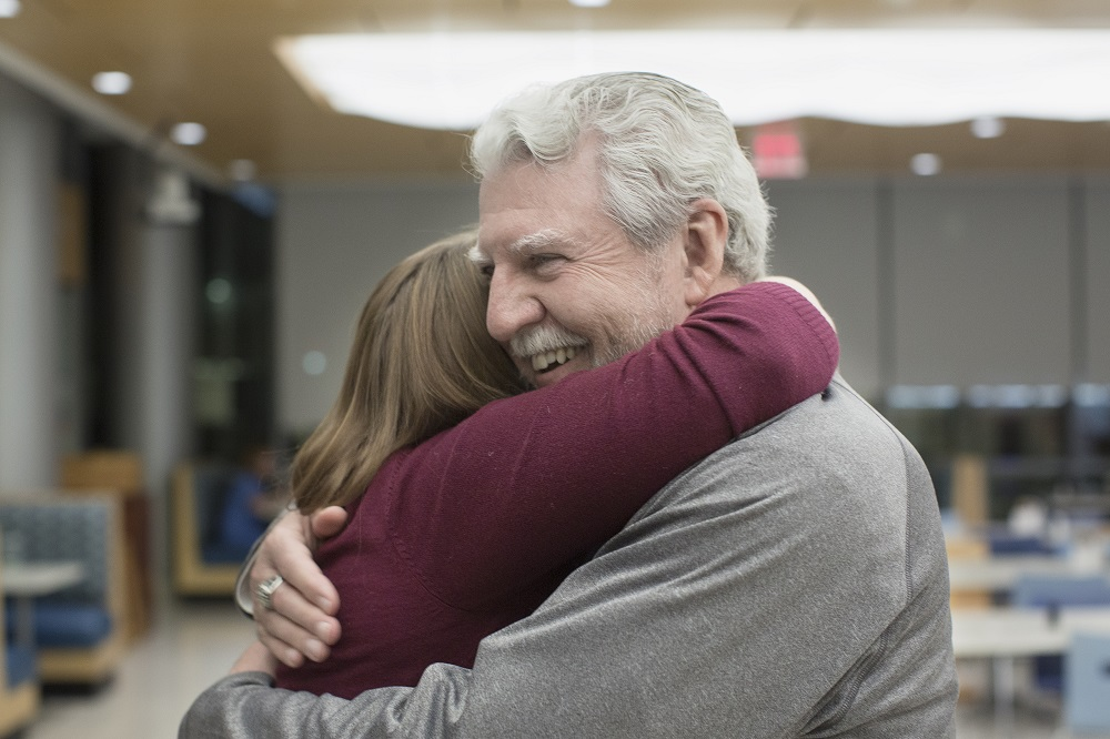 "Ed Frederick hugs Dr. Elizabeth Werley at the first ""See Me Now"" program. Ed has white hair and a moustache and is wearing a gray sweatshirt. Dr. Werley is wearing a long-sleeved sweater. Behind them are cafeteria tables and chairs. A large light fixture is above them."