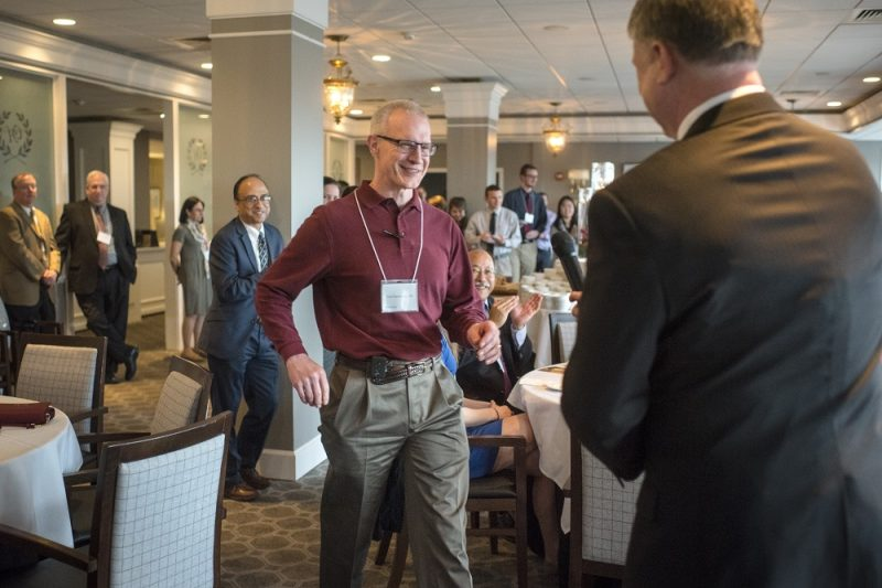 Paul Sherbundy, bespectacled man, smiles as he walks toward a man in a suit. All around Sherbundy, people in formal business attire smile and applaud or look on. They are in a conference room with upholstered chairs at circular tables.