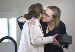 Sue Glod wraps an arm around Dr. Gisoo Ghaffari. Both women grasp box which contains the career mentoring award.