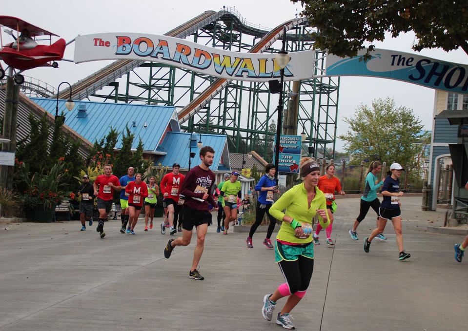 Mutiple runners running through an amusement part.