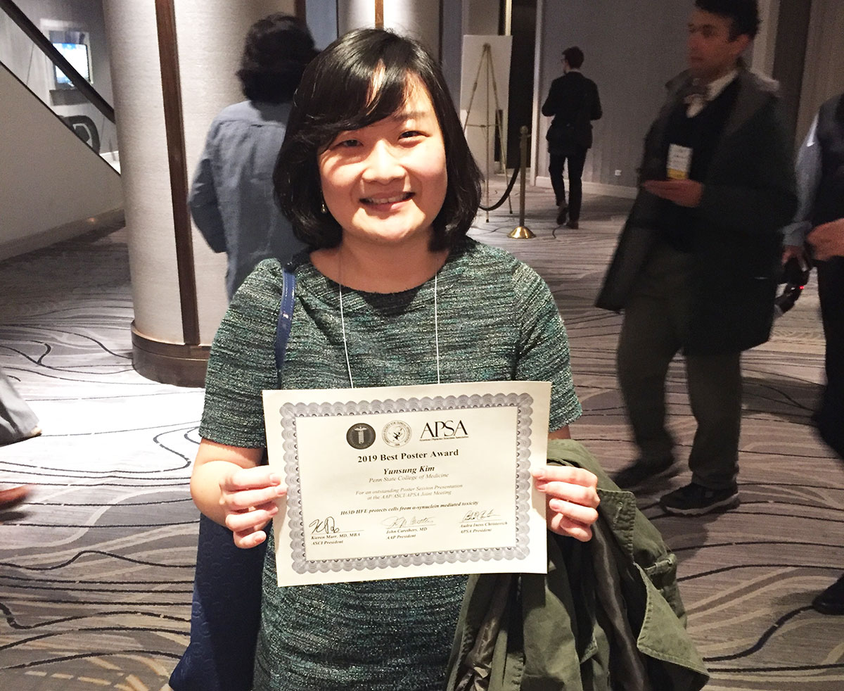 A woman is seen in a conference lobby holding a certificate.