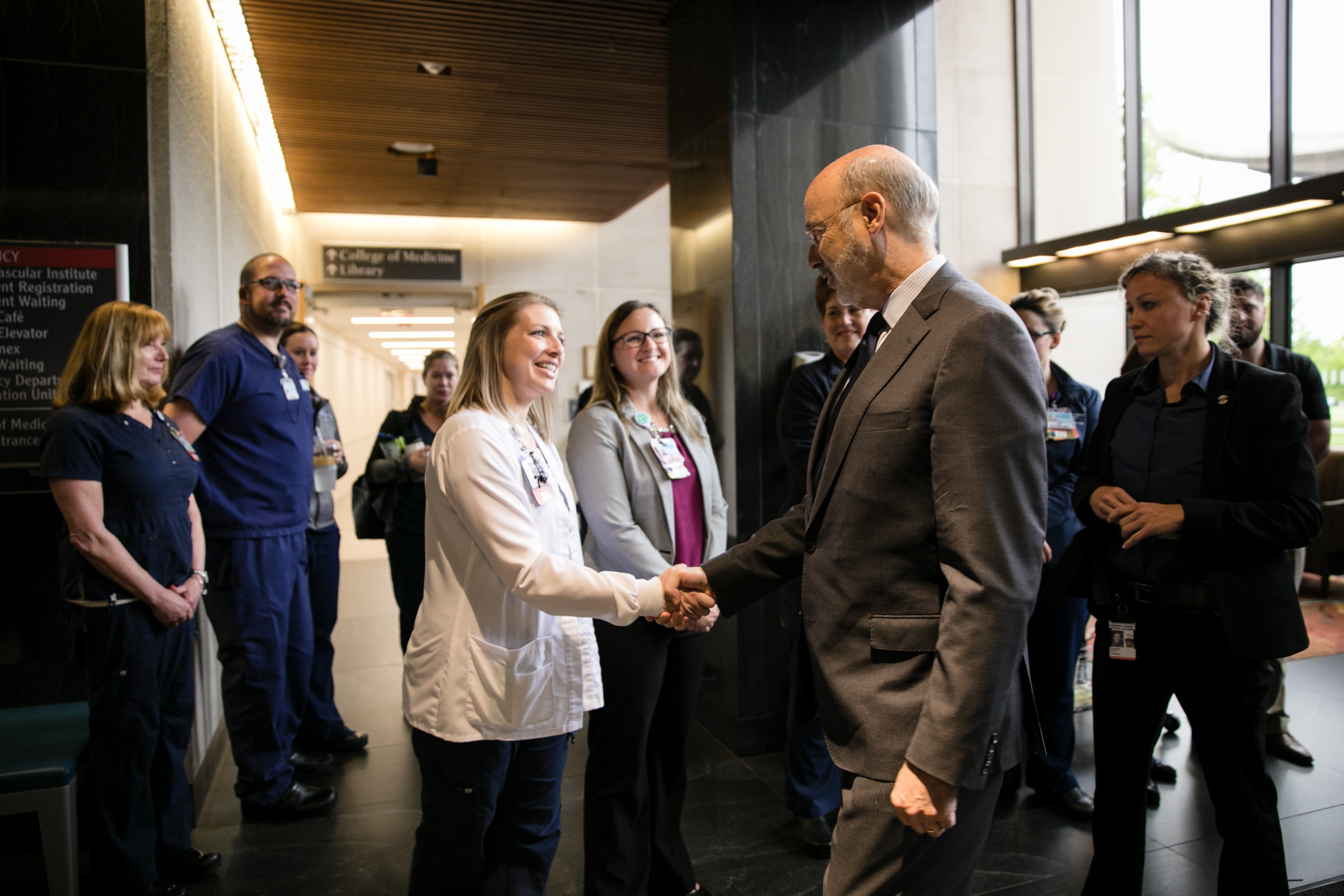 Gov. Tom Wolf, wearing a suit, shakes hands with a woman wearing a medical jacket. Other people in professional and medical attire look on. A hallway and large windows are in the background.