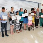 Fourteen people – 10 children and 4 adults – stand in a row to pose for a photo, all of them smiling. Each child holds an award certificate.