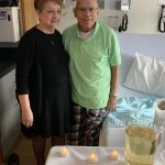 Bernadine and Charles Mineweaser stand in a hospital room with their arms around each other and smile. In front of them is a table with a cake, tea lights and a pitcher of sparkling grape juice. Next to Charles is a hospital bed, and equipment is behind them. Bernadine is wearing a dress, and Charles is wearing a polo shirt and plaid pajama pants.