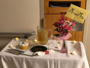 "A table in a hospital room is covered in a white tablecloth and has a cake, tea lights, a pitcher of sparkling grape juice and a vase with flowers. In the vase is a card with ""Mr. and Mrs"" written on it."