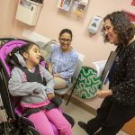 Dr. Laura Murphy, pediatrician with Penn State Children's Hospital's Pediatric Complex Care Program, smiles and bends down to greet her patient, Brinda Rizal, who is in a wheelchair. Brinda, who has braids and is wearing a sweatshirt and pants, is strapped into the wheelchair and looks up at Murphy, who is wearing a polka dotted shirt and pants and wears a stethoscope around her neck. Brinda's mother, Basudha Rizal, wearing glasses and a printed top and pants, is sitting in a chair against the wall. She smiles at her daughter. A soap dispenser, pamphlet rack and folders are hanging on the wall of the exam room.