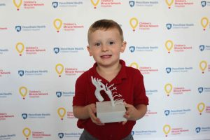 A young boy in a polo shirt holds up a plastic heart model. The step-and-repeat background has Penn State Children's Hospital and Children's Miracle Network Hospitals logos.