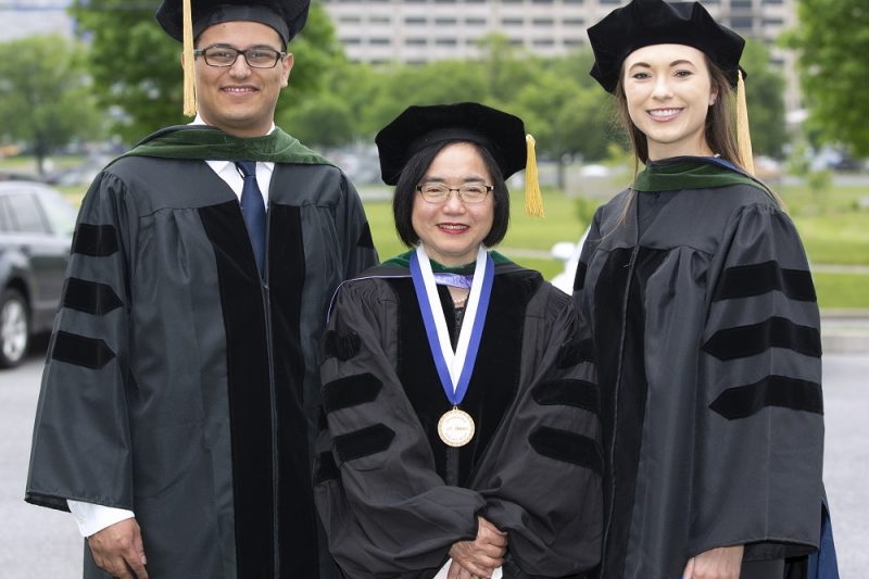 Dr. Peter Zaki, Dr. Shou Ling Leong and Dr. Sarah Stovar stand in a row in commencement caps and gowns.