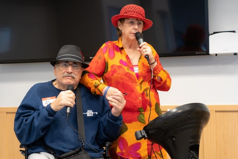 "Al Dolatoski and his wife Joyce hold hands and hold microphones as they sing Sonny and Cher's ""I Got You Babe"" during the LVAD Celebration of Life. Al is sitting in a wheelchair and wearing a sweatshirt and hat. He has an LVAD hanging by a strap around his shoulder. Joyce is wearing a flowered dress and hat."
