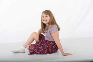 A young girl sits with her body facing away from the camera, but her head is turned toward the camera, smiling. She leans on her left arm.