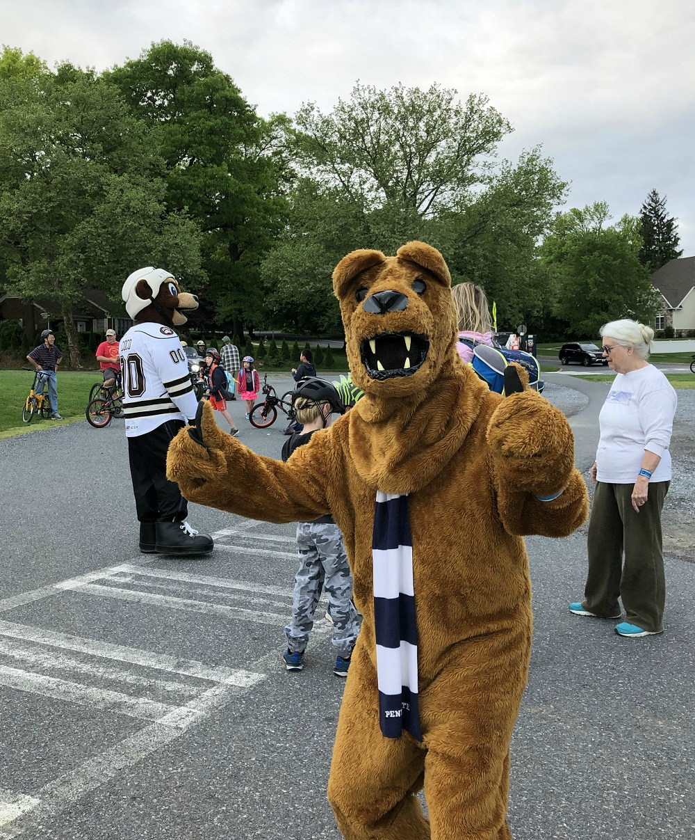 Someone in a costume dressed as the Penn State Nittany Lion gives a thumbs up sign. Behind him people on bicycles gather in a parking lot. A man dressed as the Hershey Bear's mascot, Cocoa, stands among them.
